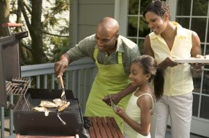 Family Barbecuing Chicken at Home