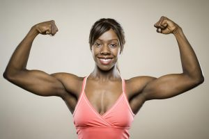 Portrait of a young woman flexing her muscles
