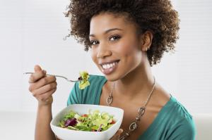 Close-up Of Beautiful African American Woman Eating Salad At Home