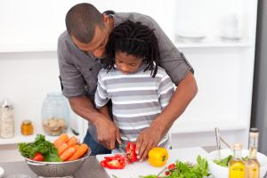 Loving father helping his son cut vegetables in the kitchen