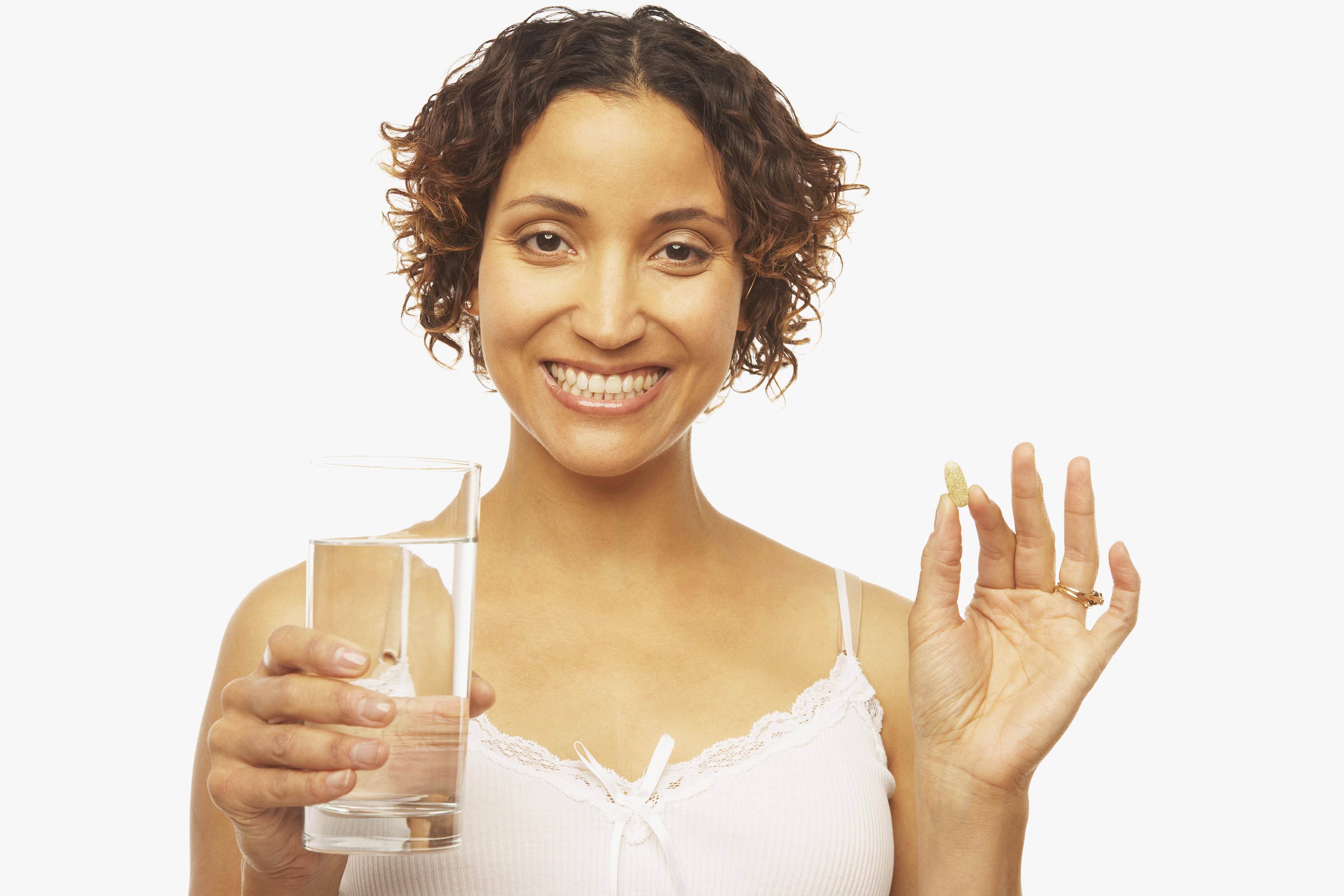 Mixed Race woman holding vitamin