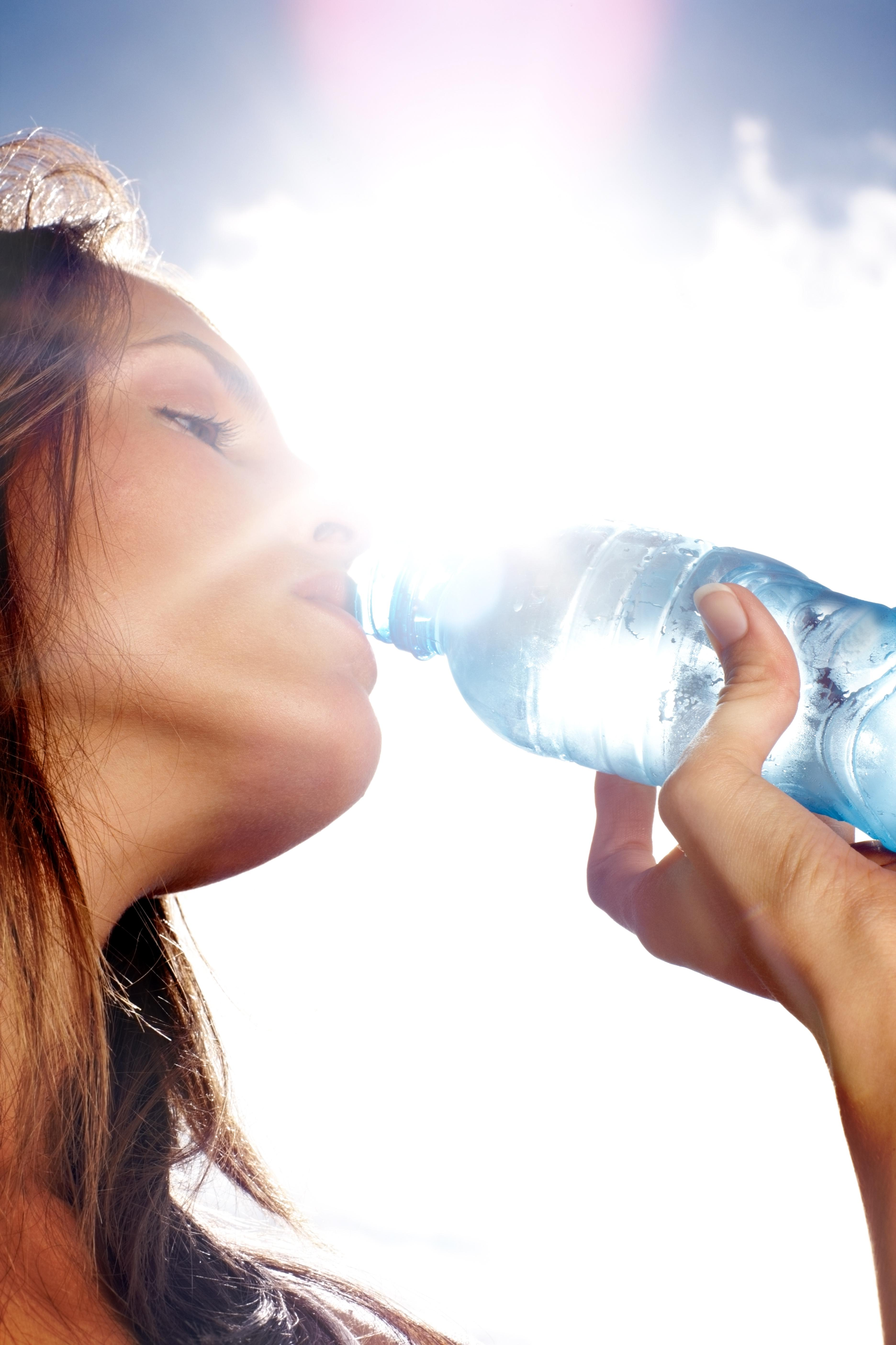 Thirsty woman drinking water on a sunny day