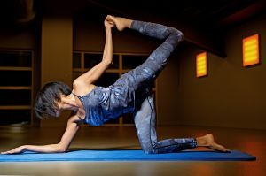 Beautiful brunette woman in yoga position at gym