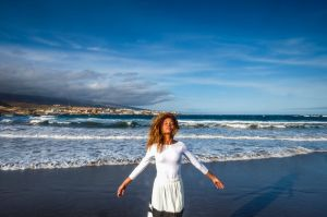 Spain, Tenerife, woman with closed eyes standing on the beach