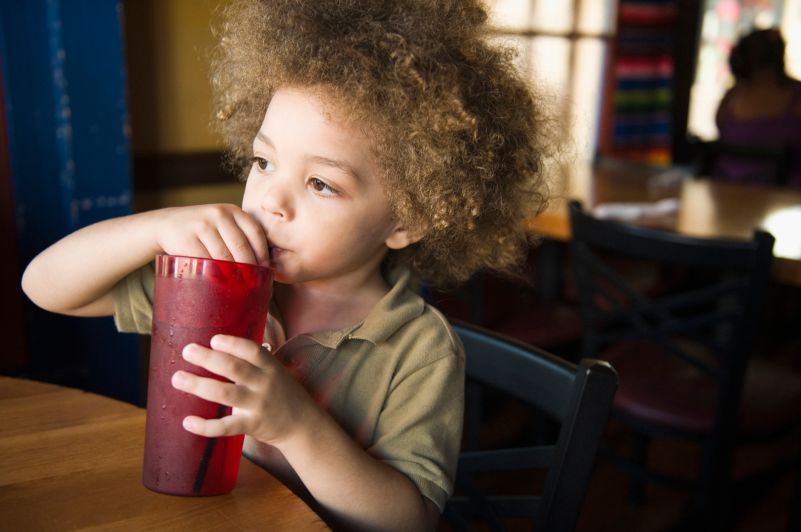 Mixed race boy drinking sofa in restaurant
