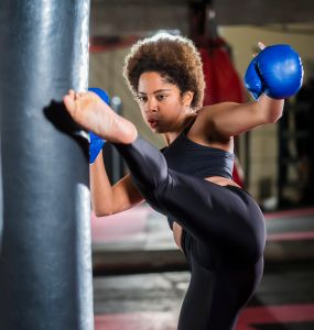 Young african woman training at gym, boxing