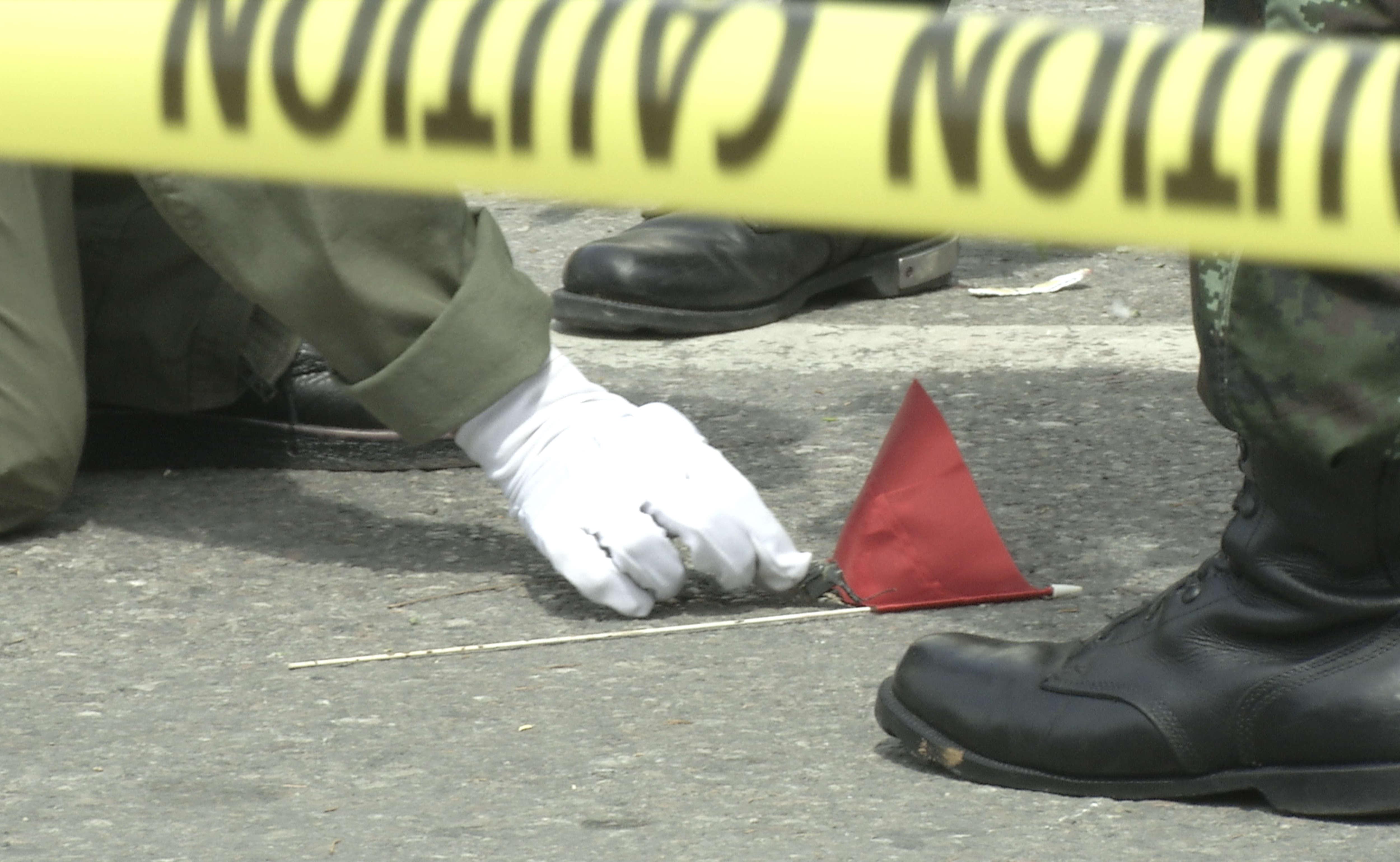 Thai police crime scene investigators search near the clock...
