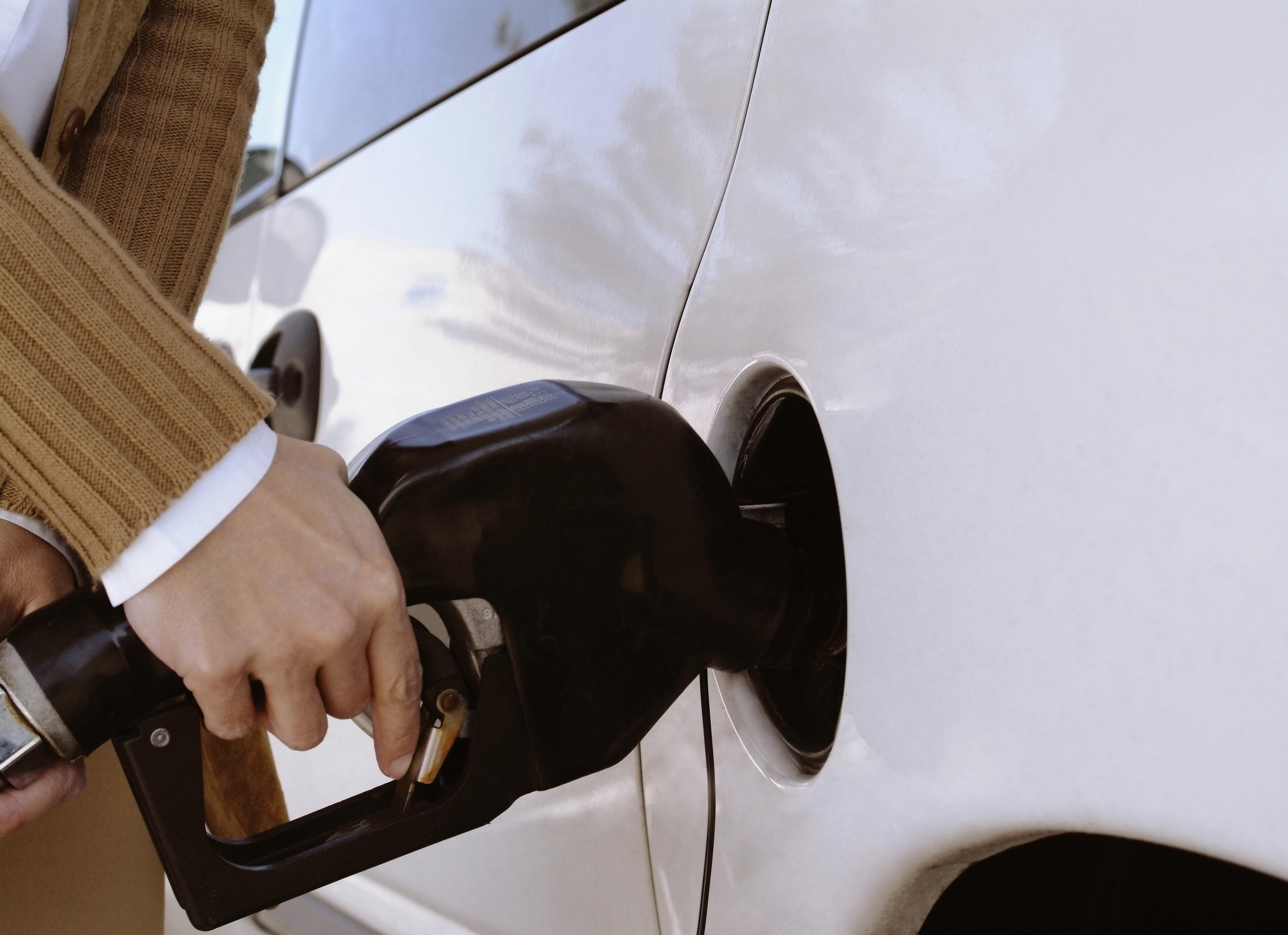 Woman putting gas in the tank of her car, extreme close-up