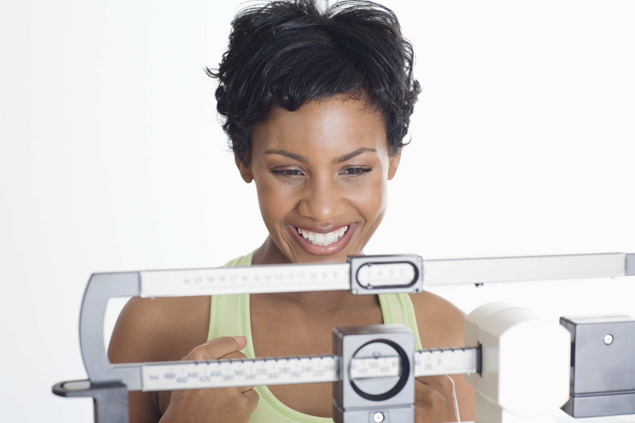 Close up of an African American Woman on a scale and looking happy.