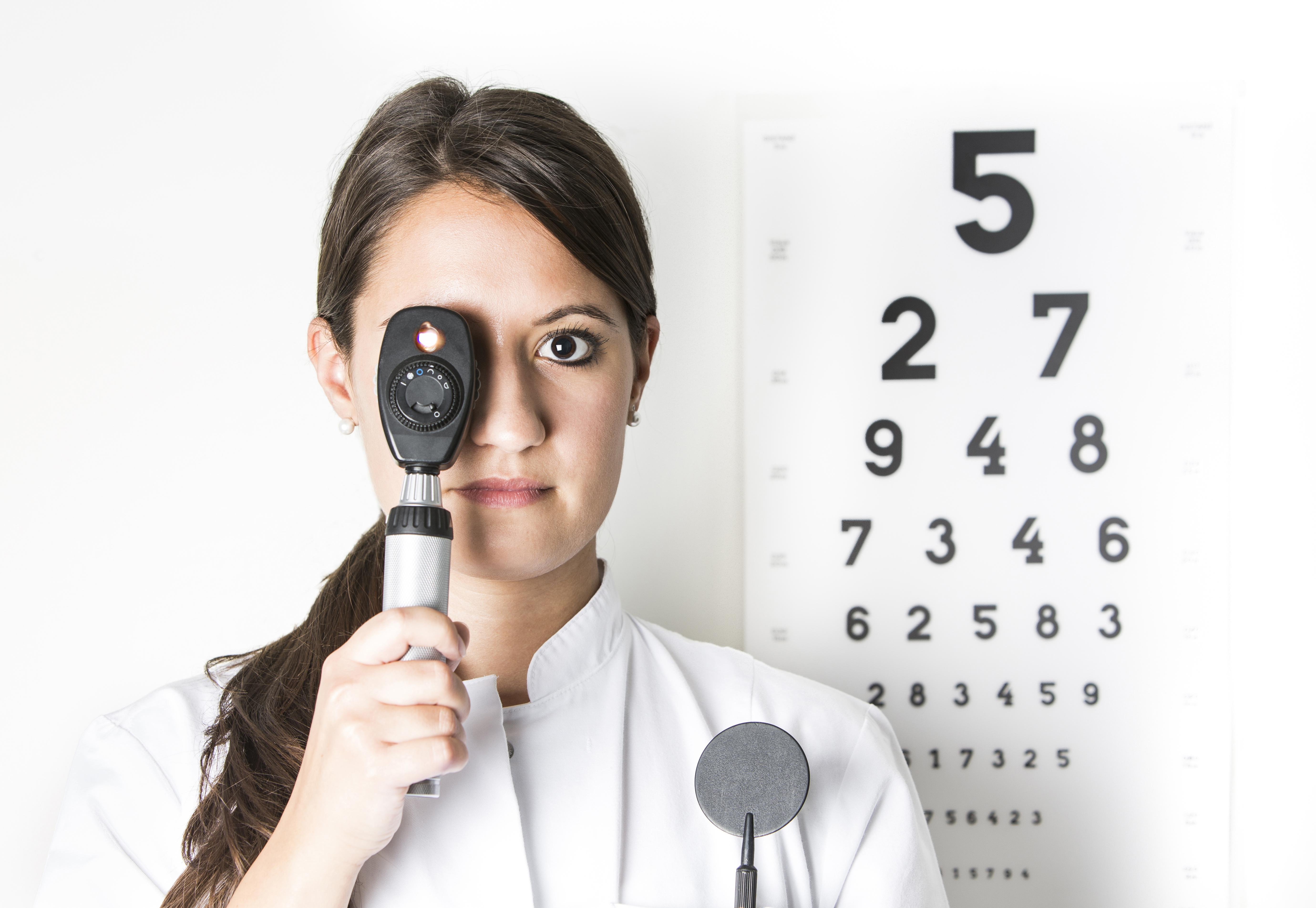 Portrait of young woman looking through ophthalmoscope, close up