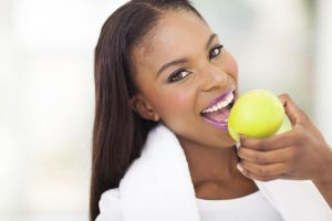 healthy african woman eating apple