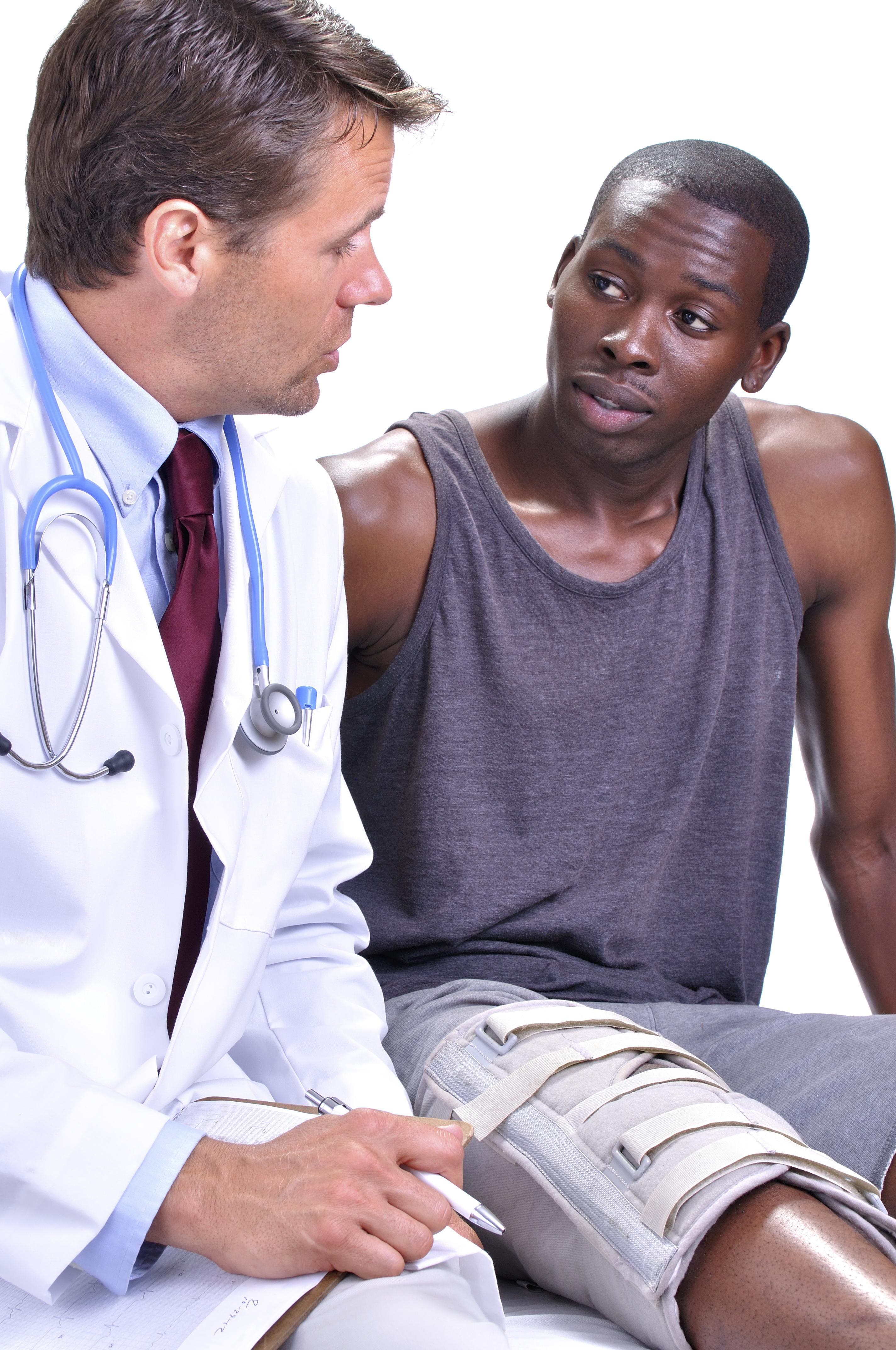 Medical doctor meets with young black male patient with leg brace in clinic with white background