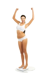 Portrait Of Young Woman Flexing Muscles While Standing On Weight Scale Against White Background